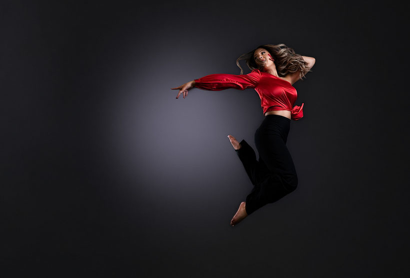 high school girl in black pants and red one sleeved silky top jumping mid air and pointing back behind her