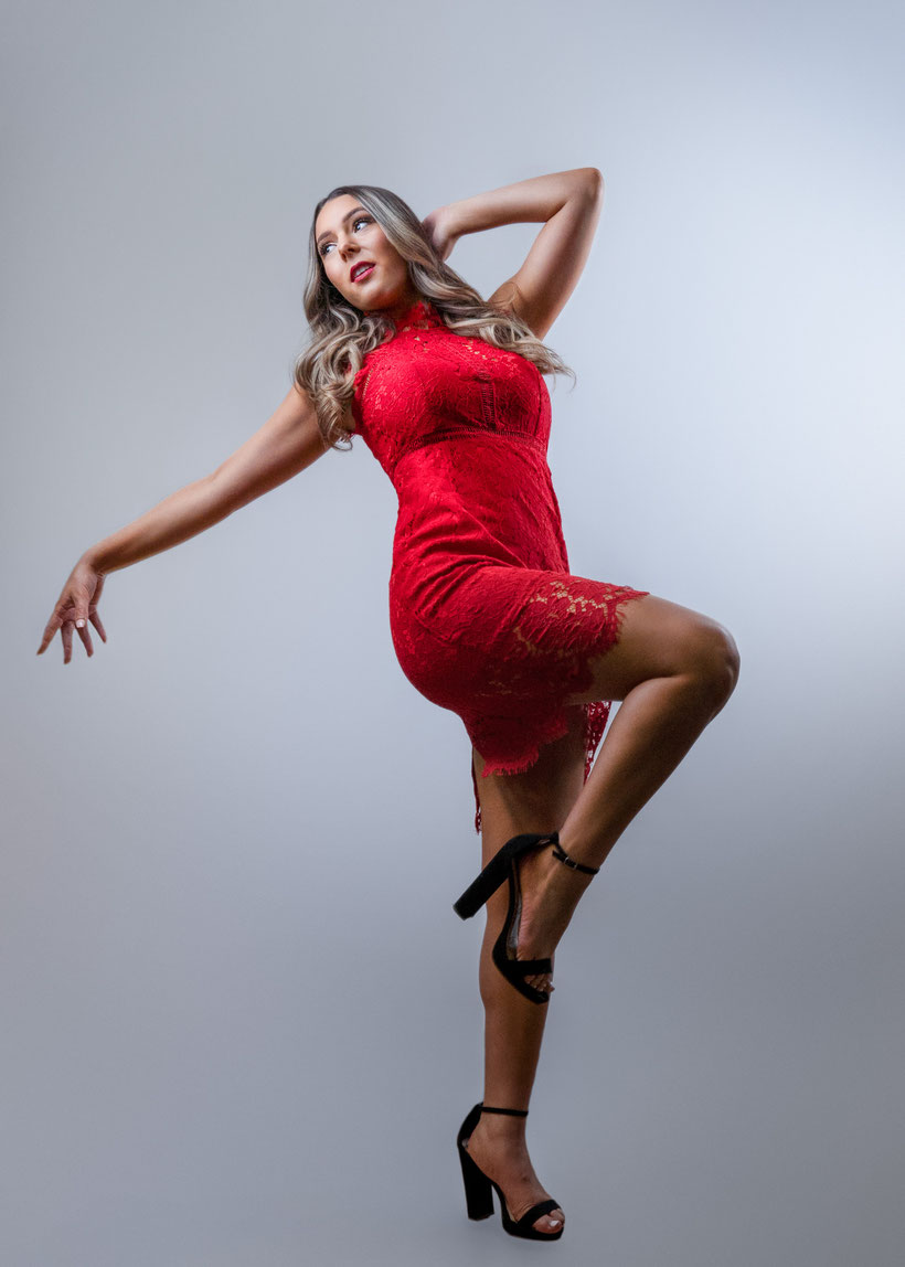High school girl in red lace dress kicking one knee up towards the right while leaning back and point towards the left