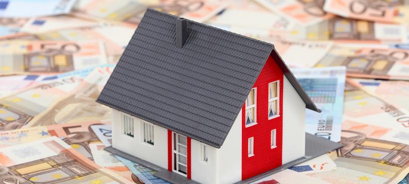 Miniatur Haus das auf Geldscheinen steht