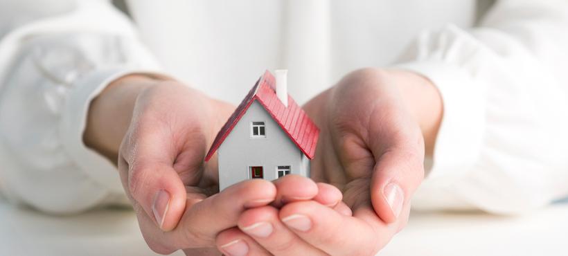 Miniatur Haus, das sich in zwei Händen befindet