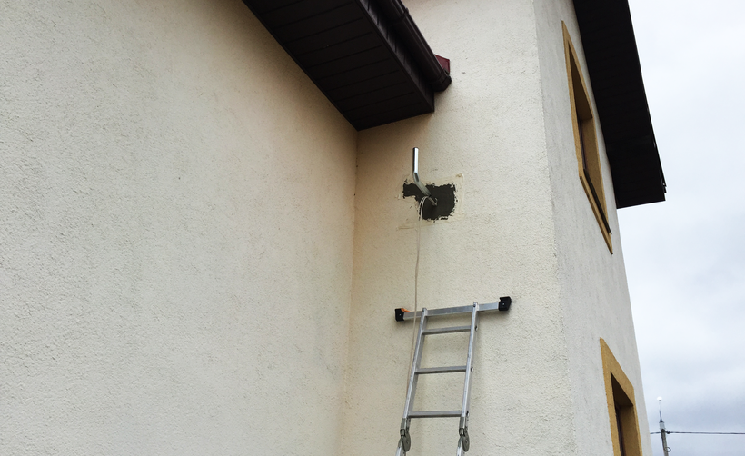 Оштукатуренный фасад после установки кронштейна