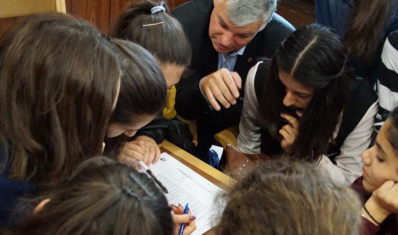 Bürgermeister Heuer, graue Haare, dunkles Sakko, steckt mit 8 jungen Mädchen die Köpfe über einer Tagesordnung zusammen