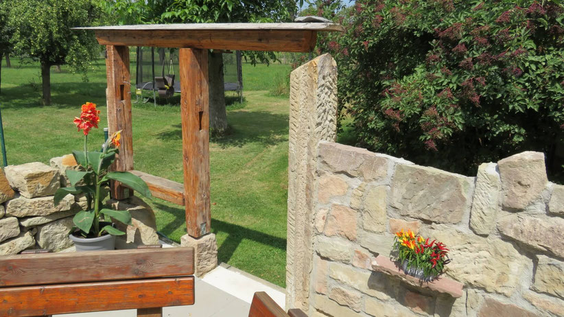 Der Torbogen ist um ein Element erweitert, welches wie ein Fenster wirkt. So bietet sich vom Sitzplatz aus ein schöner Blick in den Spielbereich im Garten.