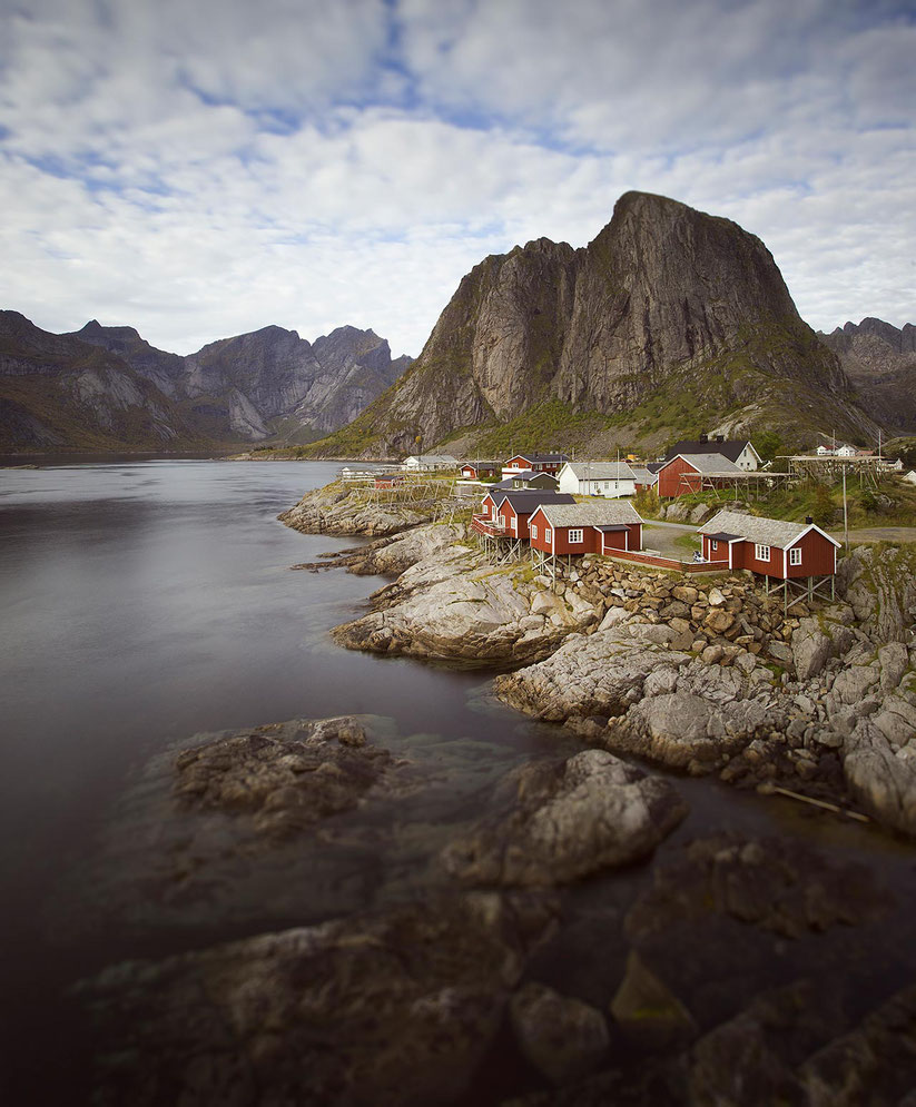 Red Fishermen houses in beautiful landscape with ocean, mountains, tilt shift exposure, Lofoten Islands, Norway, 1280x1547px