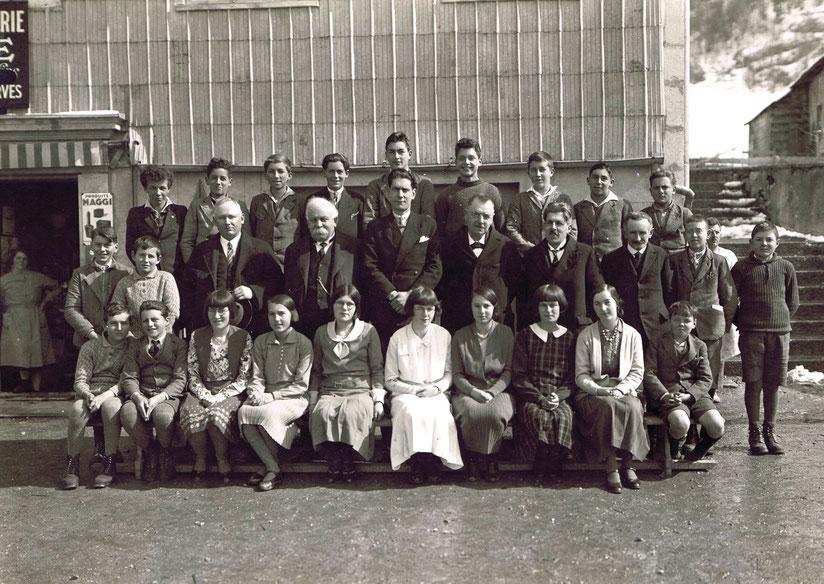 Les élèves de la primaire-supérieure du Pont en 1932. L'instituteur Georges Molles se trouve exactement au milieu, encadré par ces Messieurs les membres de la Commission scolaire, toujours très sérieux. En arrière-plan, l'école, avec la boulangerie au rez