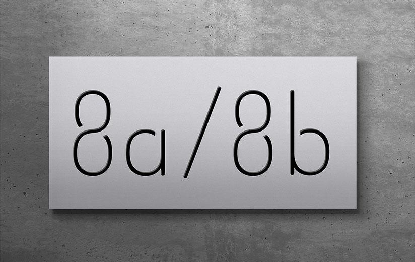 """konturgeschnittene und schwarz hinterlegte Doppelhaus-Hausnummer """"8a / 8b"""" in eloxiertem Aluminium"""