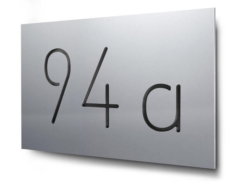 Hausnummer 94b als Konturschnitt in 3 mm Aluminium, schwarz hinterlegt