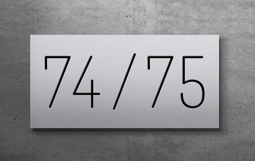 """konturgeschnittene und schwarz hinterlegte Doppelhaus-Hausnummer """"74 / 75"""" in eloxiertem Aluminium"""