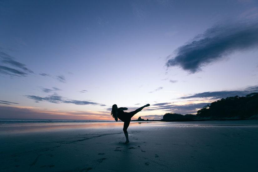 Eine Frau macht einen Karatetritt am Strand. Es ist Abend und die Sonne ist untergegangen.