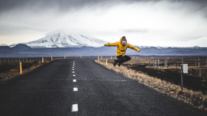 Junger Mann in gelber Trainingsjacke springt auf asphaltierter Straße in Island. Bild von Madara Parma auf Unsplash.