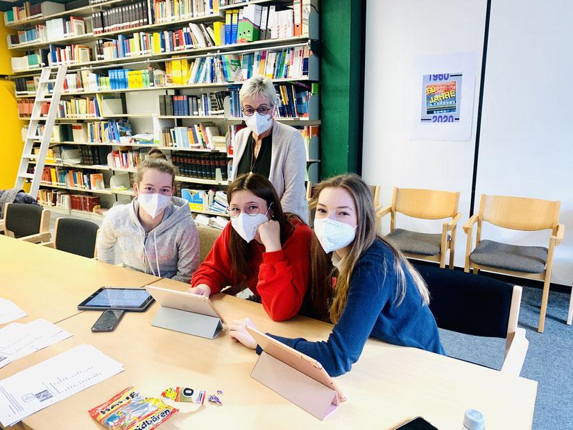 """An iPads wurden die einzelnen Filmsequenzen für den KvGG-Wettbewerbsbeitrag """"Laten we samen een duurzaam stapje doen!!"""" zusammengeschnitten. Das Foto zeigt Marie, Lana und Annika mit Niederländischlehrerin Monika Janßen."""