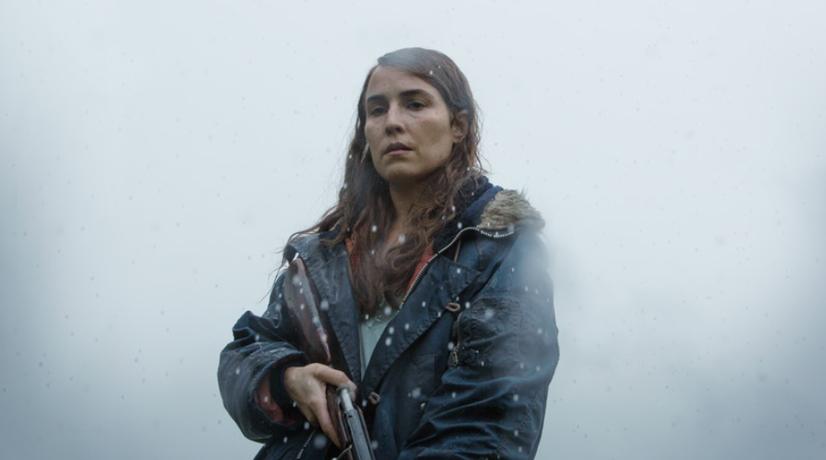Frau steht mit Gewehr im Schnee. Szene aus dem Trailer zum Film. Screenshot: Youtube.