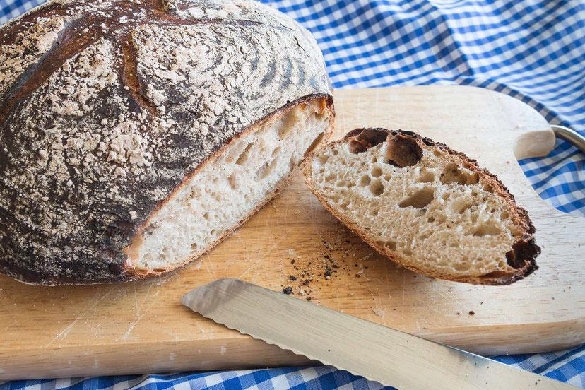 Selbstgebackenes Weizen-Sauerteigbrot angeschnitten auf Holzbrettchen-Rezept bei www.mjpics.de © Jutta M. Jenning