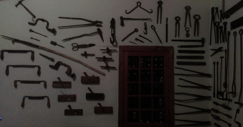 Red wine storage, old tools on the wall of the bar, South AFrica.
