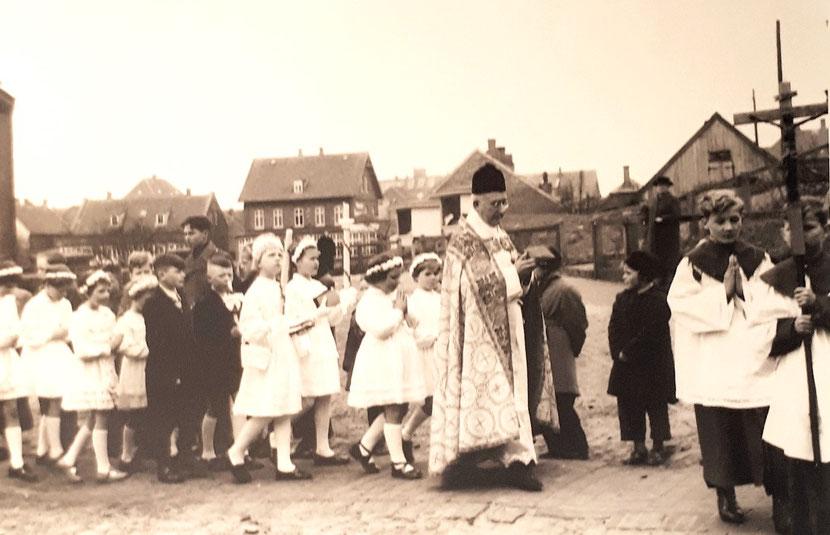 Pastor August Obst und die Kommunionkinder  ziehen feierlich zur Kirche. 1955 oder 1956   Uza Wessels,  Gerdi Kautz,  Ursula Kämpf,   Edo Hodes,  Gerd Sabrowski.