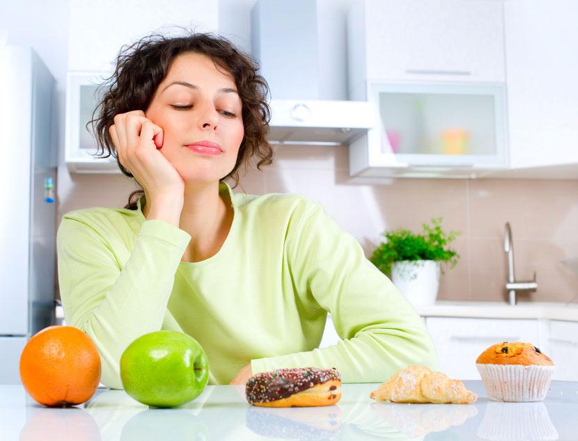 Frau überlegt einen Donut anstatt einen Apfel zu essen