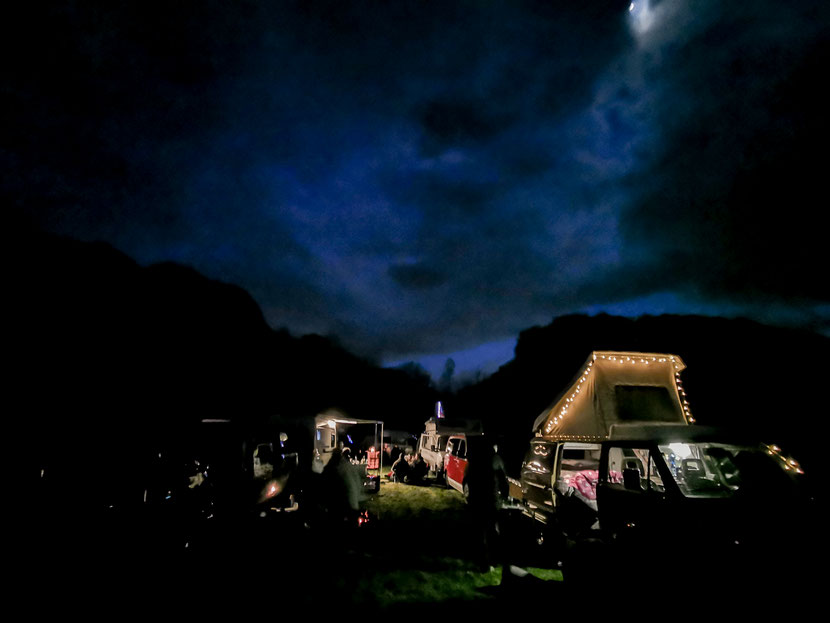 Nachts bot sich ein großartiges Bild von wunderschön beleuchteten Campern und Vans