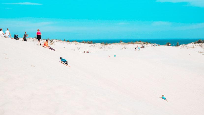 Sand surfing in Leba Poland sand dunes