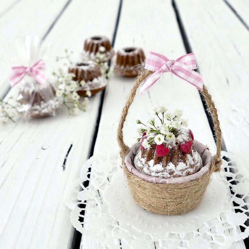Kleines, selber gemachtes Körbchen gefüllt mit Mini Gugelhupf dekoriert mit Schleierkraut und roten Herzchen