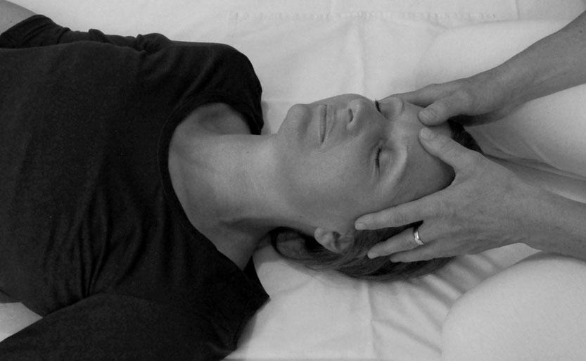 Gundi Schachl berührt die Klientin bei einer Shiatsu-Massage am Kopf.
