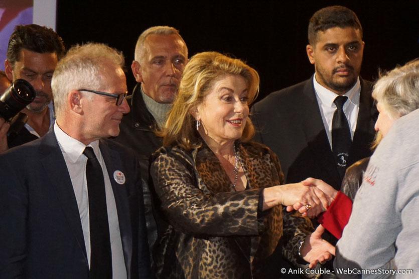 Catherine Deneuve, escortée par Thierry Fremaux, saluant une admiratrice, lors de la cérémonie de Clôture du Festival Lumière 2016  - Halle Tony Garnier de Lyon - Photo © Anik Couble