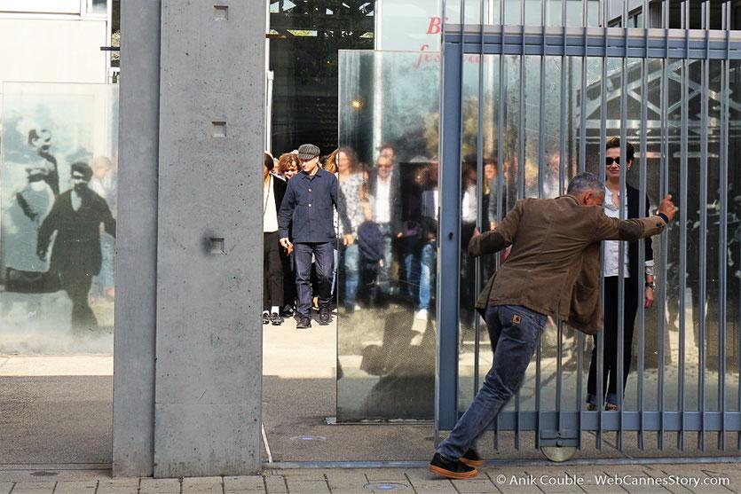 Sami Bouajila ouvrant les grilles de l'Institut Lumière pour laisser sortir Emmanuelle Devos et les invités, participant au tournage du remake de la Sortie des Usines Lumière, dirigé par Wong Kar-wai - Festival Lumière 2017 - Lyon - Photo © Anik Couble