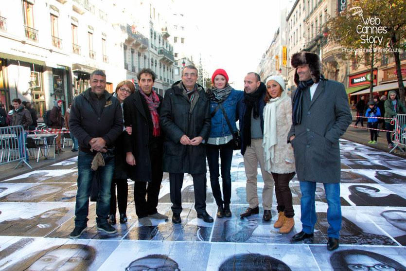 """Charlotte Le Bon et Jean-Jack Queyranne, entourés des marcheurs de 1983,Toumi Djaïdja, Arbi Rezguin, Farid L'Haoua ainsi que d'Ali Kismoun et Farida Boudaoud, lors de l'inauguration du projet """"Inside Out"""" de l'Artiste JR - Lyon  2013 - Photo © Anik COUBLE"""