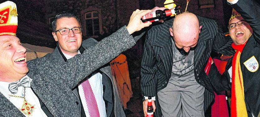 In einem eher jecken als feierlichen Akt wird der designierte Prinz Marcel Künstler von Stadtkommandant Rüdiger Fröschen, Bürgermeister Tim Grüttemeier und Komitee-Vizepräsident Michael Bartz mit Ketschenburger Bier getauft.