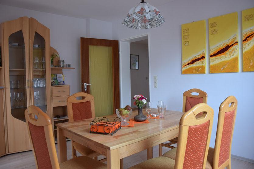 Tisch mit vier Stühlen, Vitrine, halbrunde Durchgangstür
