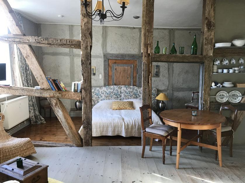 Blick in die Ferienwohnung mit dem Bett im Zentrum. Altes Fachwerk trennt Schlaf- und Wohnbereich.