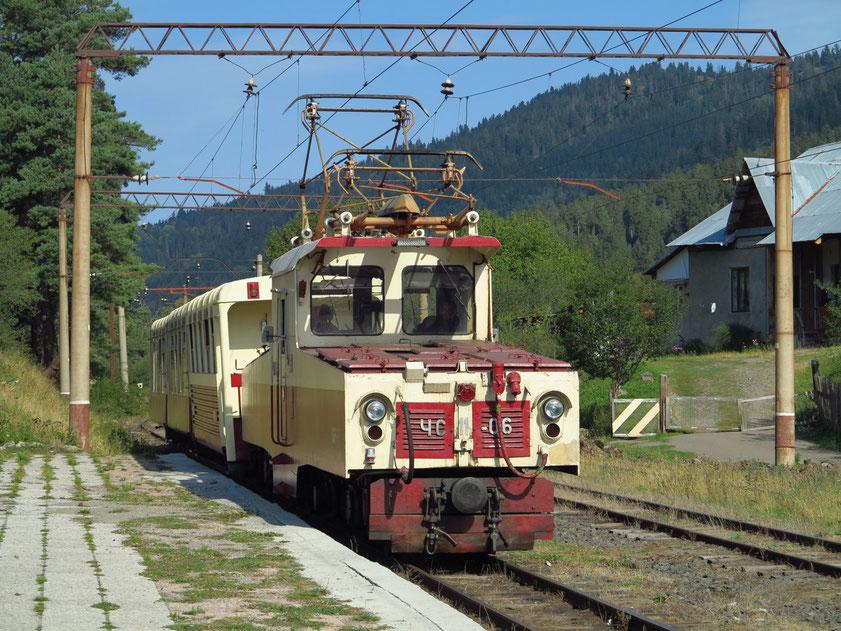 Die Elektrolokomotive (SŽD-Baureihe ЧС11) aus der ehemaligen Tschechoslowakei mit zwei Personenwagen fährt in den Bahnhof von Bakuriani ein.