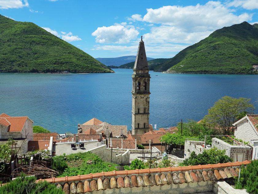 Blick von der Straße oberhalb von Perast auf die Kleinstadt mit dem 55 m hohen Glockenturm von Sv. Nikola, im Hintergrund die Verbindung der Bucht zum Meer