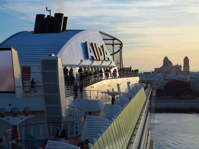 Ablegen um 18:00 Uhr. Ausfahrt aus dem Hafen und Blick bei Sonnenuntergang achtern zur Silhouette der Stadt Cádiz