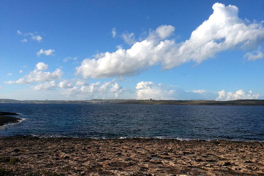 Blick vom Ramla Bay Resort auf die Felsenküste und jenseits des South Comino Channels zu den Inseln Comino und Gozo (links)