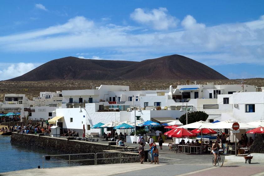 Abschied von La Graciosa. Blick vom Schiff zurück auf Caleta del Sebo. Im Hintergrund der Vulkan Montaña del Mojon mit 188 Metern Höhe.