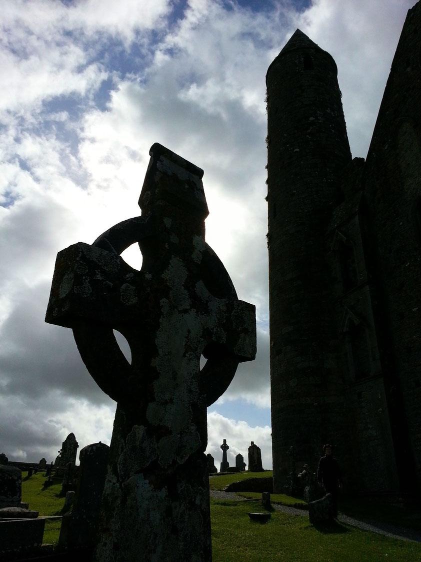 Irische Kreuze beim Rock of Cashel, rechts der 28 m hohe Rundturm