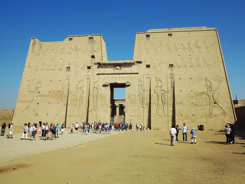Pylon des Tempels von Edfu, mit Aussparungen für Fahnenstangen. Die Götter Horus und Hathor blicken nach außen auf zwei Großreliefs an jeder Fassadenseite, wo ihnen der Pharao Ptolemaios XII. (Neos Dionysos) Gefangene als Opfer darbringt.