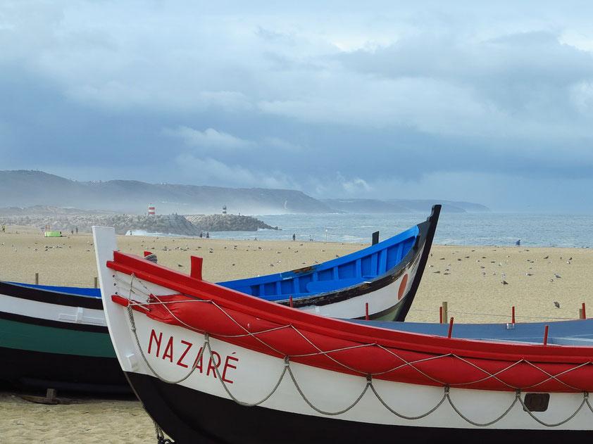 Alte Fischerboote am Sandstrand von Nazaré. Früher wurden diese Boote von Ochsen auf den Strand gezogen.