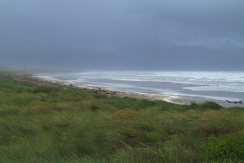 """Inch Beach auf der Dingle-Halbinsel. Die Berge des """"Ring of Kerry"""" im Hintergrund sind wolkenverhangen."""