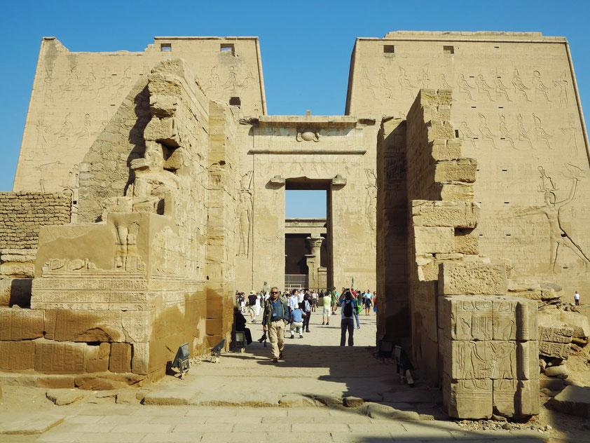 Teil des Mammisi von Edfu und dahinter der Edfu-Tempel