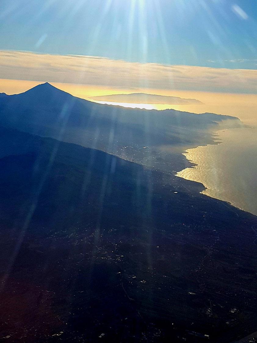 Abschied von den Kanarischen Inseln bei Sonnenuntergang: Blick aus dem Flugzeug auf Teneriffa mit dem Pico del Teide, dahinter die Inseln La Gomera und El Hierro