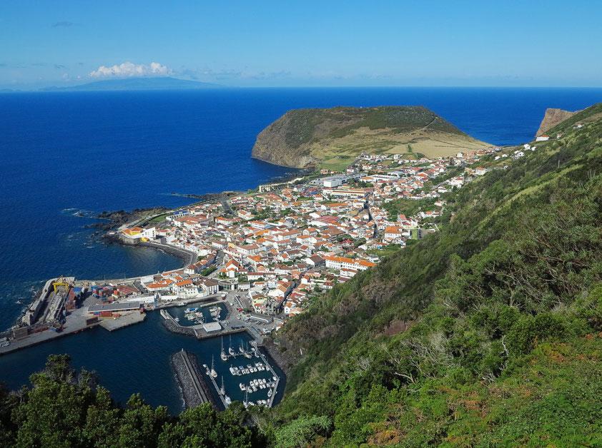 Blick auf Velas mit Hafen, die größte Stadt von São Jorge, am Horizont die Insel Faial