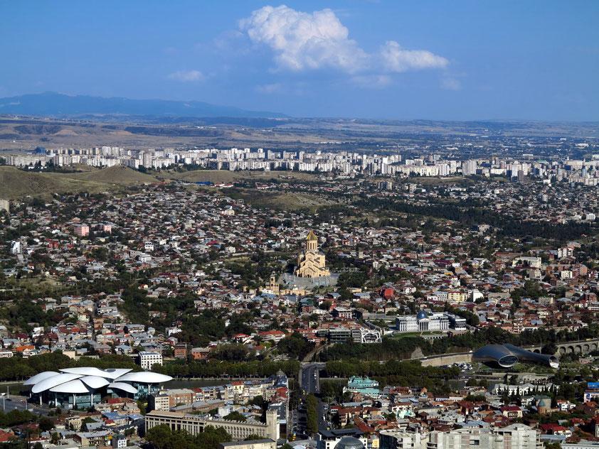Blick vom Berg Mtazminda auf Tbilisi (in der Mitte die Sameba-Kathedrale, links vorne Tbilisi Public Service Hall, rechts vorne neues Konzerthaus/Ausstellungszentrum von Massimiliano & Doriana Fuksas)