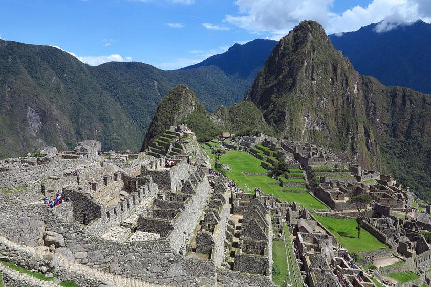 Machu Picchu. Die Inkas erbauten die Stadt im 15. Jahrhundert in 2360 Metern Höhe auf einem Bergrücken zwischen den Gipfeln des Huayna Picchu (rechts im Hintergrund)  und des Berges gleichen Namens (Machu Picchu) in den Anden über dem Urubambatal.