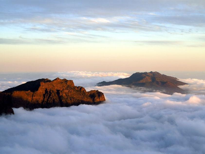Bergspitzen über dem Wolkenmeer: links der Rand der Caldera de Taburiente, rechts die knapp 2000 m hohe Cumbre Vieja,  dazwischen die bedeckte Cumbre Nueva