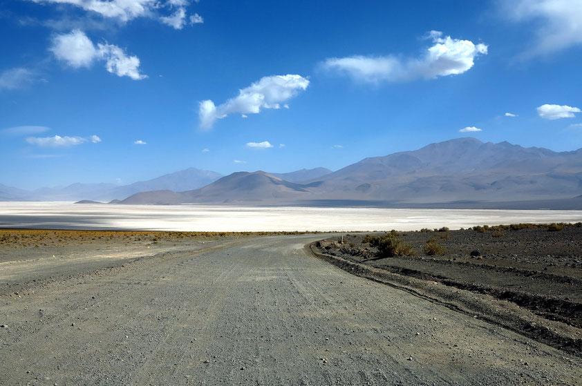 Piste zwischen Bolivien und Chile, im Hintergrund eine Salzpfanne (Salar)