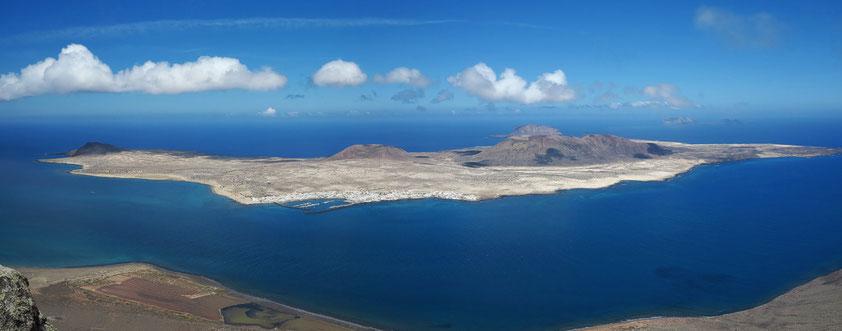 Das dunkelblaue Meer und die in hellen Pastelltönen leuchtende, nur von einigen Schatten weißer dahinfliegender Wolken bedeckte Insel Graciosa erscheinen unwirklich wie eine Vision.