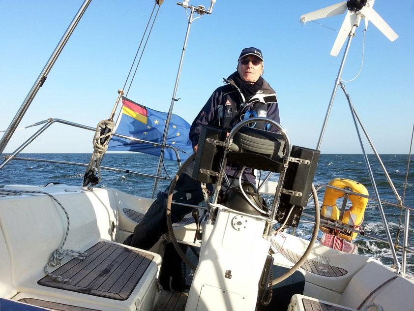 Gerd am Steuerrad seiner Segelyacht HELLA