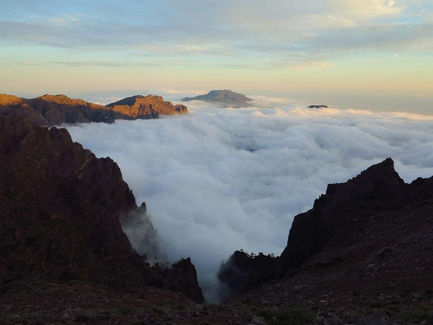 Blick bei Sonnenuntergang vom Mirador de los Andenes (2300 m) in die Caldera de Taburiente mit Wolkenmeer, im Hintergrund die knapp 2000 m hohe Cumbre Vieja