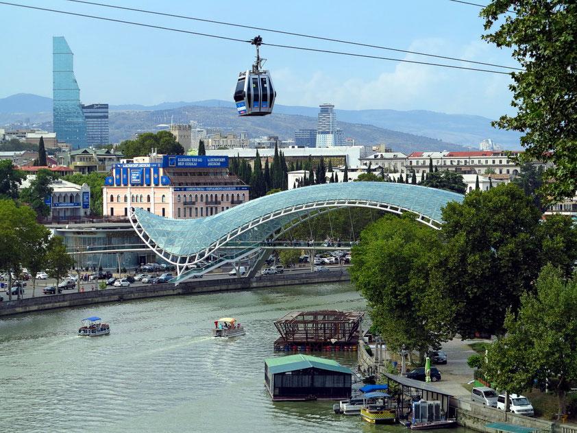 Tbilisi. Blick von der Metekhi-Brücke auf den Fluss Kura mit der Friedensbrücke (2009/2010) und auf die Seilbahn zur Burg Nariqala
